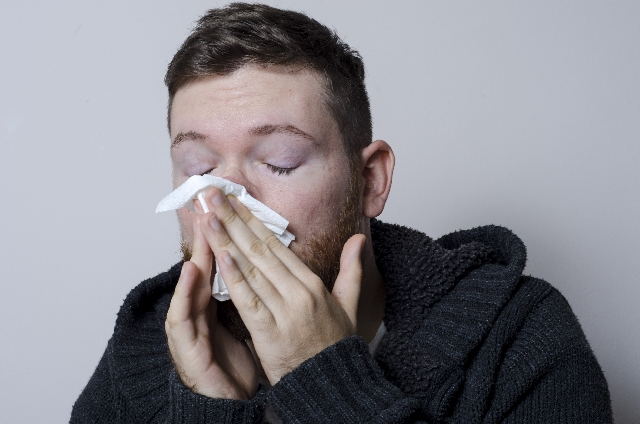 A guy sneezing